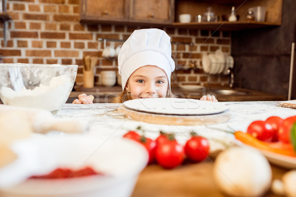 little girl making pizza dough with pizza ingredients in kitchen  Stock photo © LightFieldStudios
