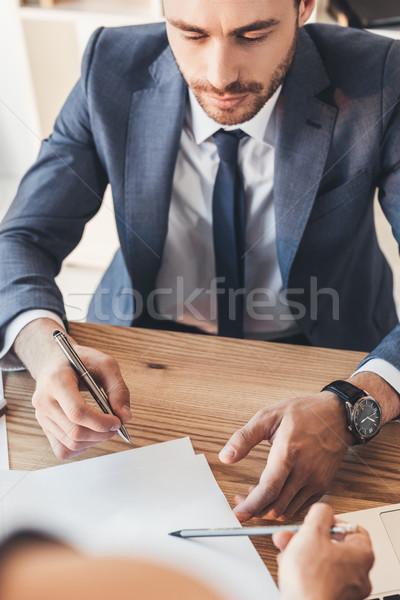 Empresario firma papeleo tiro mujer Foto stock © LightFieldStudios