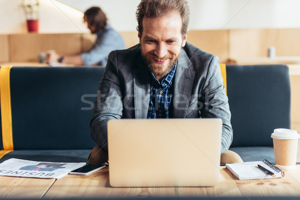 Homem usando laptop bonito sorridente barbudo café Foto stock © LightFieldStudios