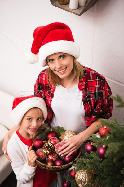 mother and daughter decorating christmas tree Stock photo © LightFieldStudios