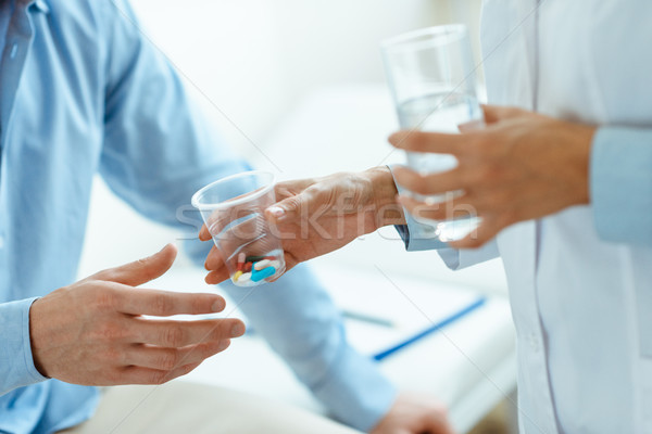 Woman handing pills to man Stock photo © LightFieldStudios