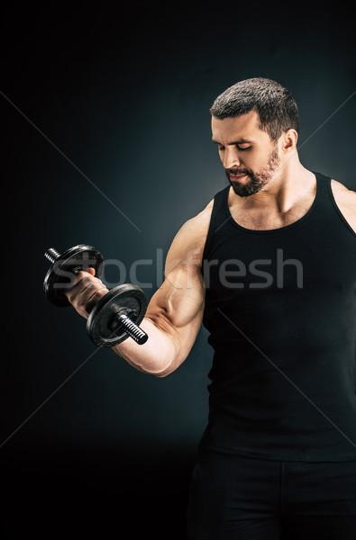 sportive man pumping muscles Stock photo © LightFieldStudios