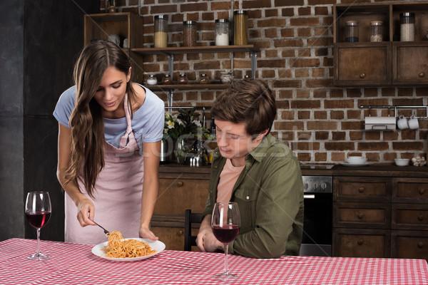 Nő főtt vacsora fiatal nő kötény fiúbarát Stock fotó © LightFieldStudios