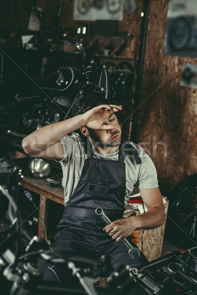 tired mechanic repairing motorbike Stock photo © LightFieldStudios