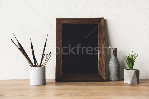 photo frame and paintbrushes on tabletop Stock photo © LightFieldStudios