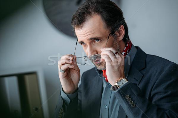 Stock photo: businessman holding eyeglasses