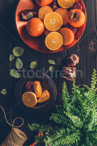 top view of persimmons with cut oranges and pomegranates on plates on wooden table Stock photo © LightFieldStudios