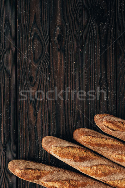 top view of arranged loafs of french baguette on wooden surface Stock photo © LightFieldStudios