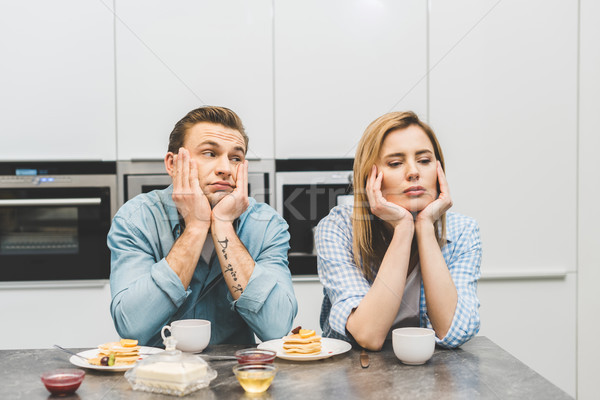 portrait of argued couple sitting at table with breakfast at home Stock photo © LightFieldStudios