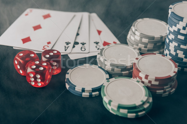 Playing cards with dice and chips on casino table Stock photo © LightFieldStudios