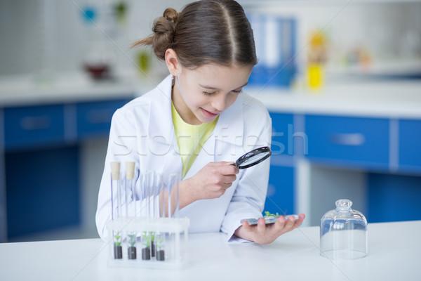 Sorridente menina cientista lupa olhando Foto stock © LightFieldStudios