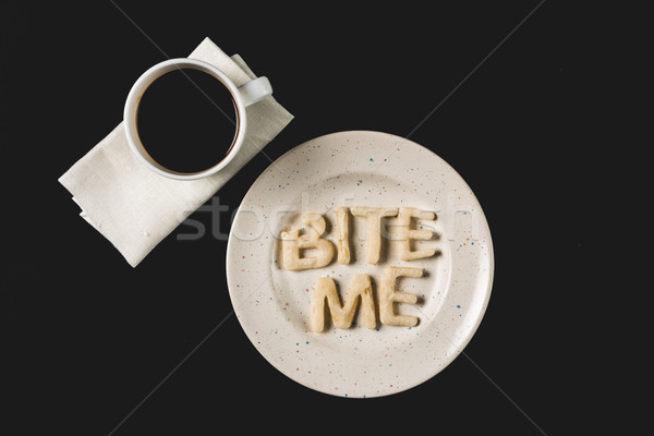 top view of lettering bite me made from cookie dough on plate with coffee cup isolated on black Stock photo © LightFieldStudios