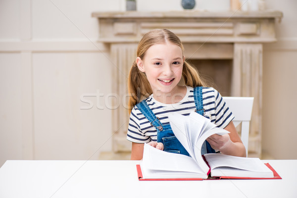 Cute preteen girl sitting at table with book and smiling at camera Stock photo © LightFieldStudios
