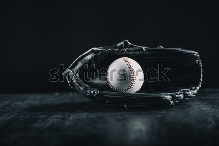Close-up view of leather baseball glove and ball on black Stock photo © LightFieldStudios