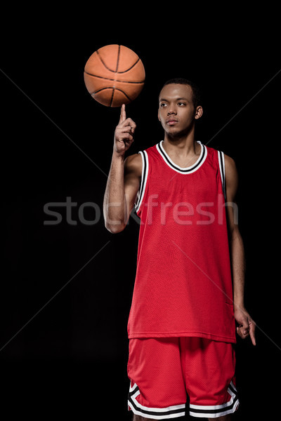 Stock photo: African american basketball player posing and balancing ball on finger on black