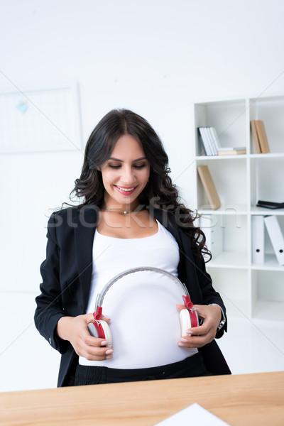 Terhes üzletasszony fejhallgató pocak boldog iroda Stock fotó © LightFieldStudios