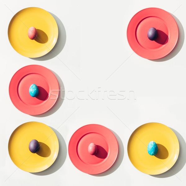 food composition with easter eggs on colorful plates with copy space Stock photo © LightFieldStudios