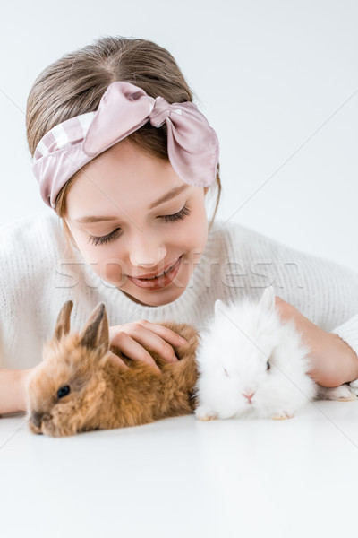 happy child playing with adorable furry rabbits on white  Stock photo © LightFieldStudios