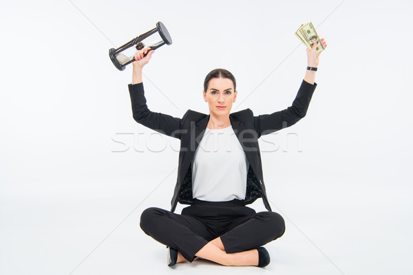 Businesswoman with hourglass and money Stock photo © LightFieldStudios