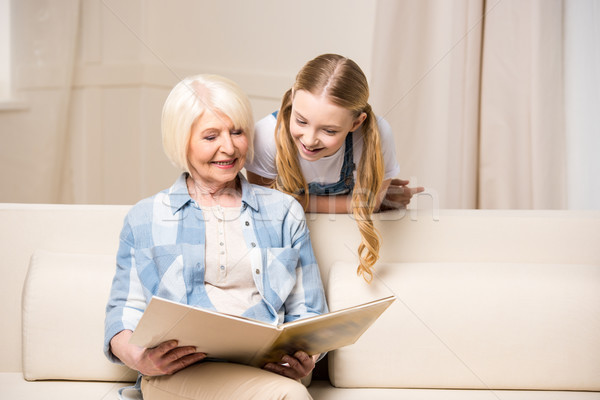 Happy grandmother and granddaughter looking at photo album at home  Stock photo © LightFieldStudios