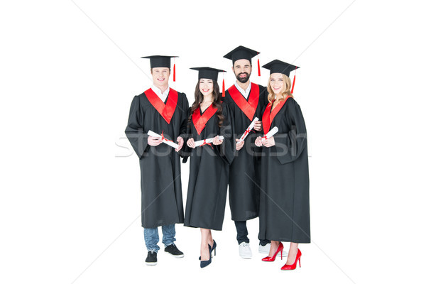 Full length front view of happy students in graduation caps holding diplomas on white Stock photo © LightFieldStudios