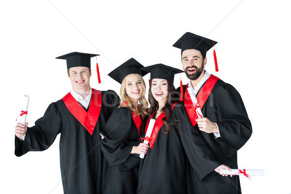 Happy young men and women in academic caps holding certificates and smiling Stock photo © LightFieldStudios