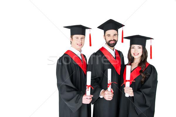 Happy students in graduation caps holding diplomas and smiling at camera  Stock photo © LightFieldStudios