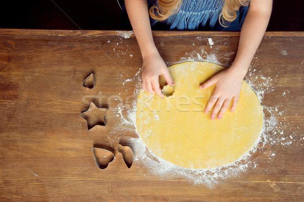 top view of girl making shaped cookies with cookie cutters on wooden table  Stock photo © LightFieldStudios