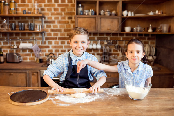 Stock photo: children making pizza dough on wooden tabletop in kitchen