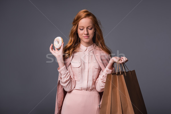 lady with donut and shopping bags Stock photo © LightFieldStudios