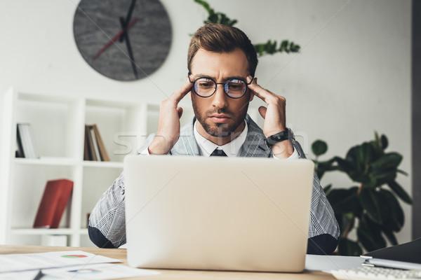 концентрированный бизнесмен ноутбука молодые очки глядя Сток-фото © LightFieldStudios