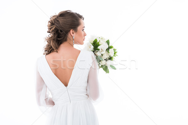 back view of bride in white dress holding wedding bouquet, isolated on white Stock photo © LightFieldStudios