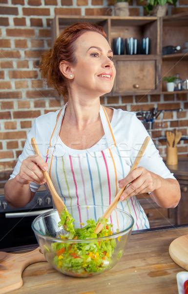 Woman mixing fresh vegetable salad Stock photo © LightFieldStudios
