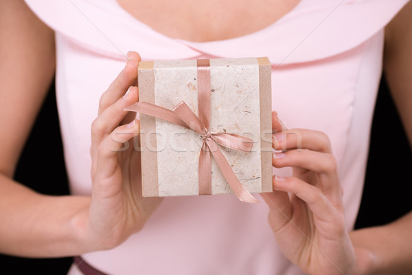 Close-up partial view of woman in pink dress holding gift box on black, international womens day con Stock photo © LightFieldStudios