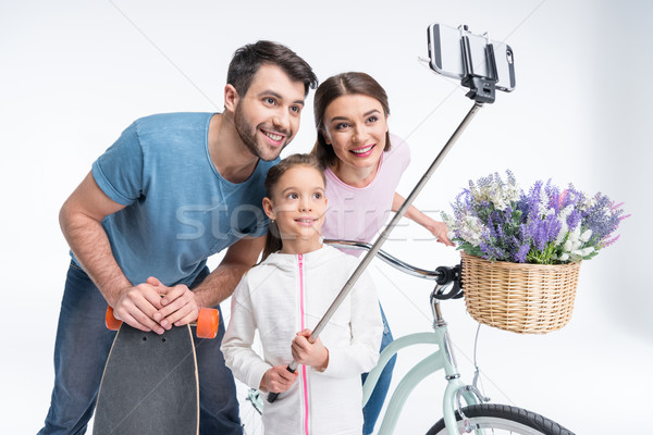 portrait of smiling family with skateboard and bicycle making selfie Stock photo © LightFieldStudios