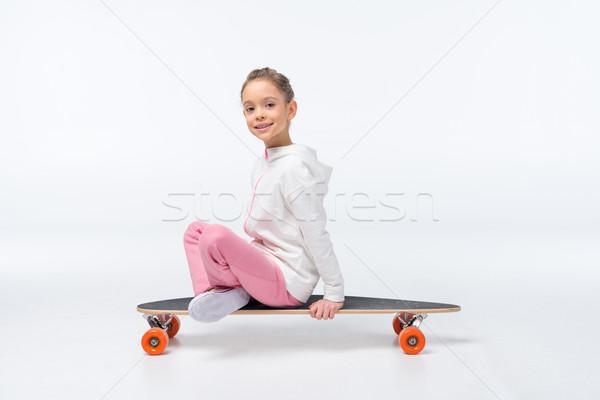 smiling girl sitting on skateboard on white Stock photo © LightFieldStudios