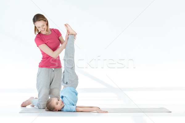 Stock photo: Side view of happy mother training daughter on yoga mat