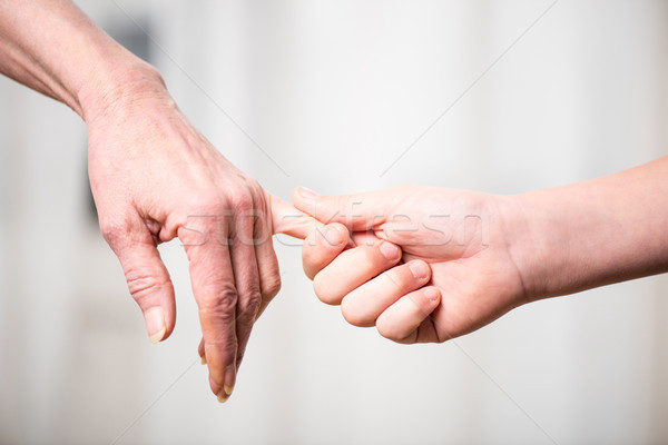 Close-up partial view of grandmother and child holding hands Stock photo © LightFieldStudios