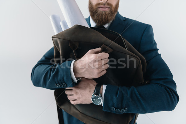 Cropped shot of young businessman hugging bag with rolled blueprints Stock photo © LightFieldStudios
