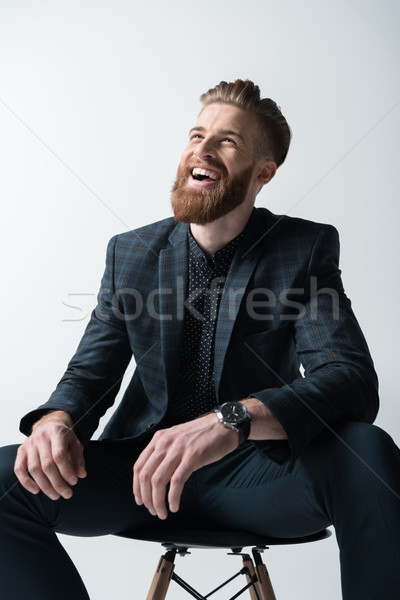 portrait of laughing stylish bearded man sitting on chair on grey Stock photo © LightFieldStudios