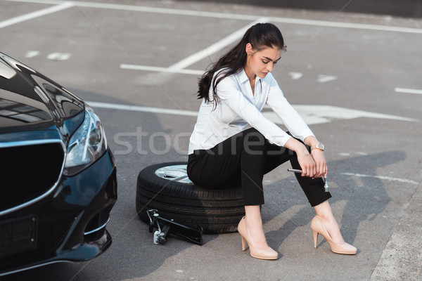 woman sitting on tire with wrench Stock photo © LightFieldStudios