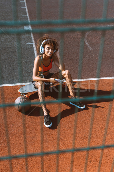 young african-american woman in sportswear listening to music in headphones and sitting on longboard Stock photo © LightFieldStudios