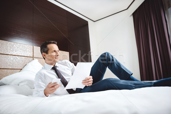 businessman on bed with paperwork and smartphone Stock photo © LightFieldStudios