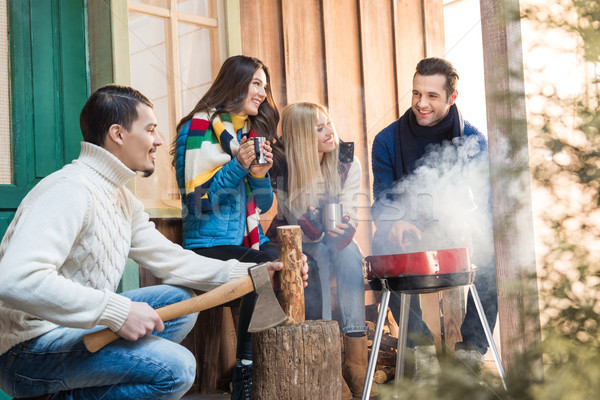 Smiling man chopping firewood with axe while happy friends drinking tea near grill Stock photo © LightFieldStudios