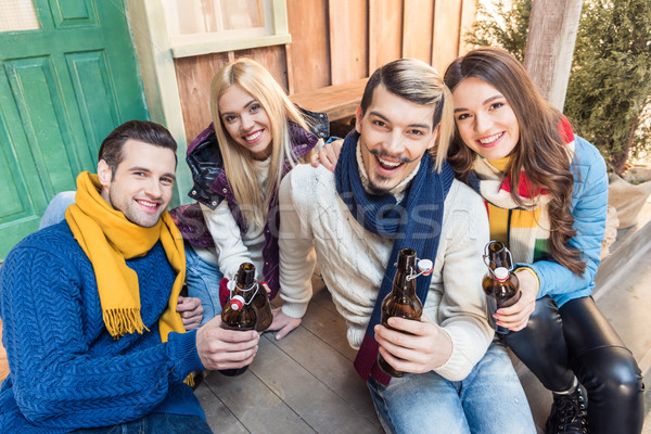 Stock photo: high angle view of smiling friends sitting on floor and drinking beer