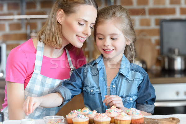 portrait of daughter and mother decorating cupcakes with confetti Stock photo © LightFieldStudios