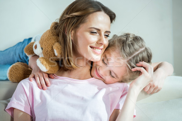 Happy mother and daughter with teddy bear hugging on sofa at home Stock photo © LightFieldStudios