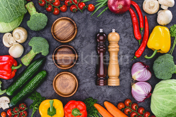 top view of fresh organic vegetables, wooden plates and containers for spices on black Stock photo © LightFieldStudios