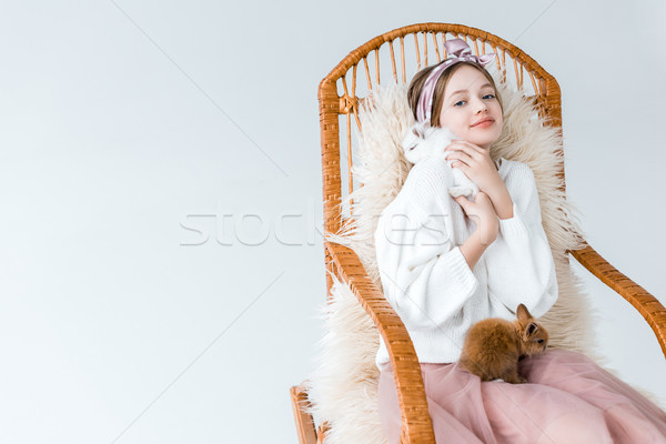 beautiful teenage girl smiling at camera while sitting in rocking chair with furry rabbits isolated  Stock photo © LightFieldStudios