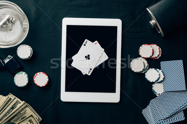 Online gambling with playing cards and chips by digital tablet Stock photo © LightFieldStudios